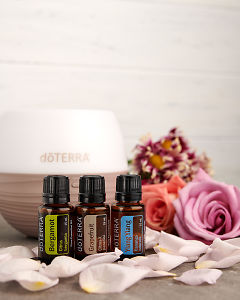 doTERRA Bergamot, Grapefruit and Ylang Ylang with a Petal  diffuser, flowers and scattered rose petals on a gray stone benchtop.