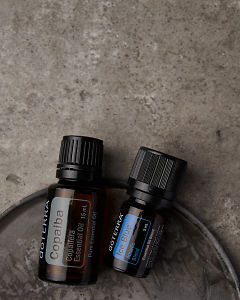 doTERRA Copaiba and Ice Blue on a gray stone background.