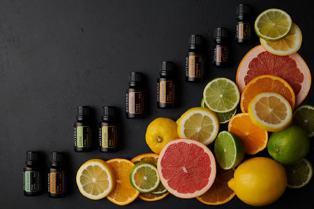 doTERRA citrus oils and slices of citrus fruit on black concrete background.