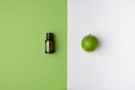 doTERRA Lime oil on green background and whole lime on white background.