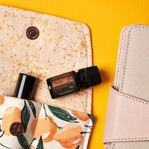 doTERRA Arise on an essential oil bag with a pink diary on a yellow textured background.