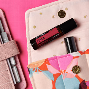 doTERRA Rose Touch on an essential oil bag with a pink diary on a hot pink textured background.