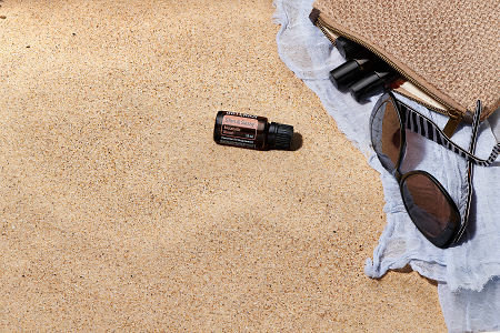 doTERRA Slim and Sassy with sunglasses, scarf and roller bottles in a clutch on the beach.