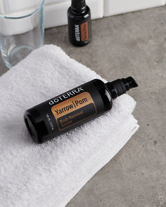 doTERRA Yarrow Pom Body Renewal Serum on a white towel  on a gray stone bathroom bench top.