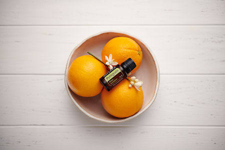 doTERRA Petitgrain in a white ceramic bowl with seville oranges and orange blossoms on a white wooden background.