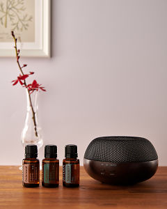 doTERRA Brevi Walnut diffuser with Cedarwood, Cypress and Siberian Fir essential oils on a side table.