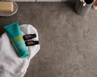 doTERRA Spa Hand and Body Lotion with Lavender and Myrrh essential oils and bathroom accessories on a white towel on a stone background.
