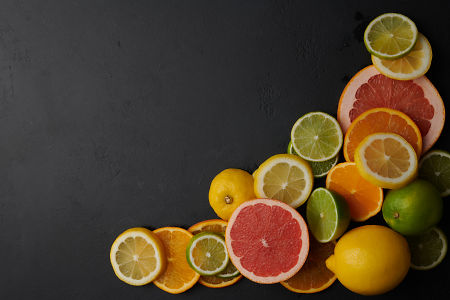 Whole lemon and lime fruit plus slices of lemon, orange, grapefruit and lime on black concrete background.