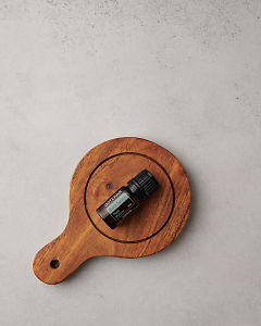 doTERRA Black Spruce on a wooden chopping board on a white stone benchtop.