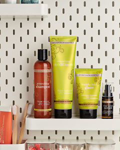 doTERRA Salon Essentials including Protecting Shampoo, Smoothing Conditioner, Healthy Hold Glaze and Root to Tip Serum on a bathroom shelf with other doTERRA products and bathroom accessories.
