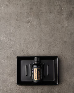 doTERRA Yarrow|Pom in a black soap dish on a gray stone background.