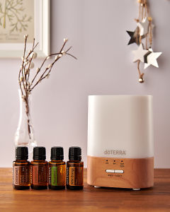 doTERRA Lumo diffuser with Cedarwood, Frankincense, Rosemary and Wild Orange essential oils and holiday decorations on a side table.