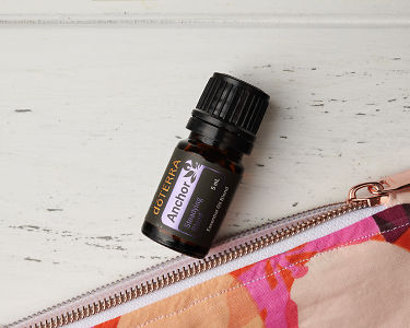 A close up of doTERRA Anchor and the corner of an essential oil bag on a white wooden background.