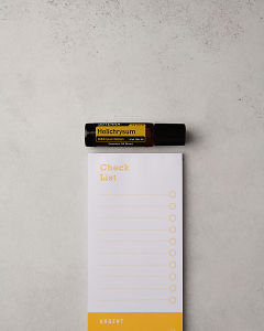 doTERRA Helichrysum Touch with a notepad on a white stone benchtop.