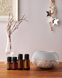 doTERRA Brevi Stone diffuser with Cardamom, Cinnamon, Clove and Wild Orange essential oils and holiday decorations on a side table.