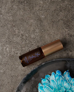doTERRA Blue Lotus Touch 4ml with flowers on a gray stone background.
