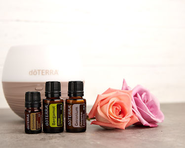 doTERRA Sandalwood, Bergamot and Geranium with a Petal diffuser and roses on a gray stone bench.