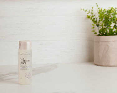 doTERRA Essential Skin Care Pore Reducing Toner on a white bench with a pot plant.