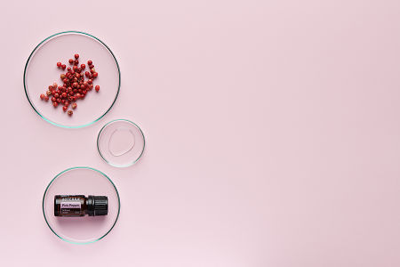 doTERRA Pink Pepper in a petrie dish with pink peppercorns and oil in petri dishes on a pale pink background.