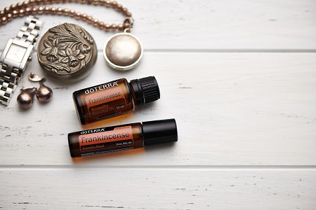 doTERRA Frankincense oil and Frankincense Touch, jewellery and trinkets on white rustic wooden background.