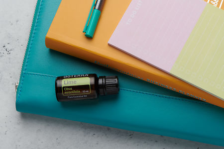 doTERRA Lime oil with business folder, planner, pen and to do list on white concrete background.
