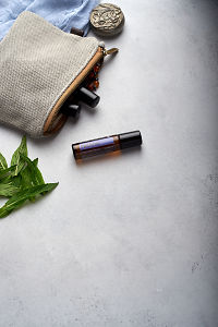 doTERRA PastTense with clutch, accessories and mint leaves on a white concrete background.