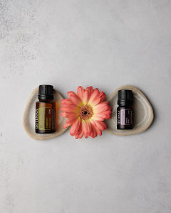 doTERRA Marjoram 15ml and doTERRA Pink Pepper 5ml with a peach colored Gerbera on a concrete background.
