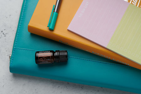 doTERRA Red Mandarin oil with business folder, planner, pen and to do list on white concrete background.