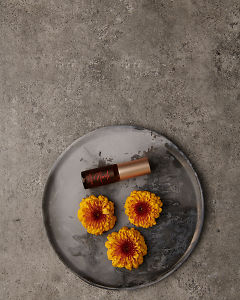doTERRA Neroli Touch 4ml on a ceramic plate with flowers on a gray stone background.