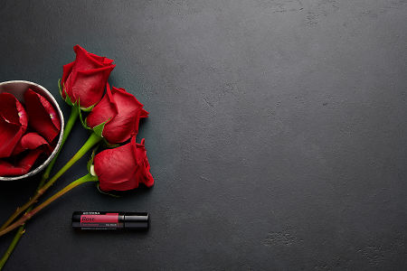 doTERRA Rose with rose stems and petals in a bowl on a black background.