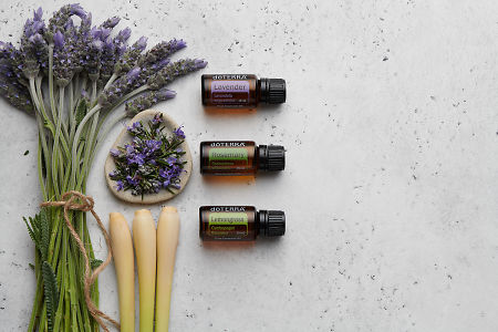 doTERRA Lavender, Rosemary and Lemongrass with lavender stems tied with twine, rosemary flowers in a dish and lemongrass stalks on a white concrete background.