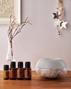 doTERRA Brevi Stone diffuser with Cheer, Clove, Grapefruit and Wild Orange essential oils and holiday decorations on a side table.