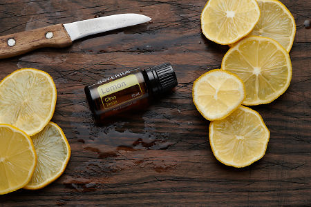 doTERRA Lemon oil, lemon slices and knife on rustic wooden chopping board.