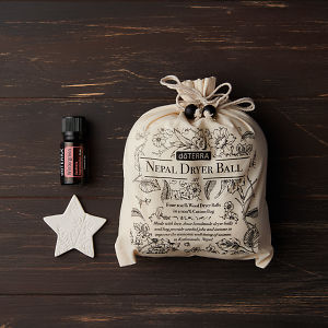 doTERRA Nepal Dryer Balls and Wintergreen essential oil with a star on a brown wooden background.