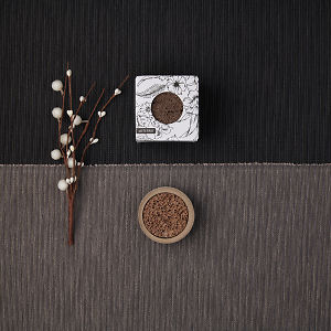 doTERRA Concrete Lava Rock Diffusers with a holiday decoration on a dark and medium gray textured background.