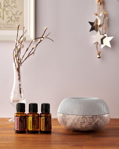 doTERRA Brevi Stone diffuser with Geranium, Lemon and Wild Orange essential oils and holiday decorations on a side table.