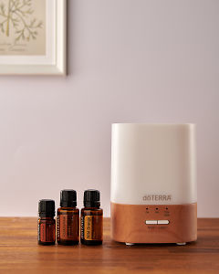 doTERRA Lumo diffuser with Cinnamon, Frankincense and Wild Orange essential oils on a side table.