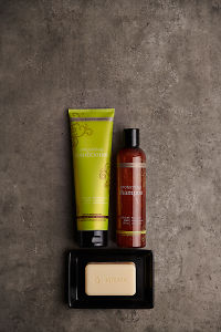 doTERRA Salon Essentials Shampoo and Conditioner  with a doTERRA Spa Moisturizing Bath Bar in a black soap dish on a gray stone bathroom bench.