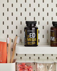 doTERRA xEO Mega on a bathroom shelf with additional doTERRA products and bathroom accessories.