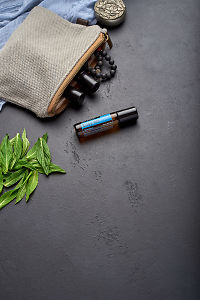 doTERRA Easy AirTouch with clutch, accessories and mint leaves on a black concrete background.