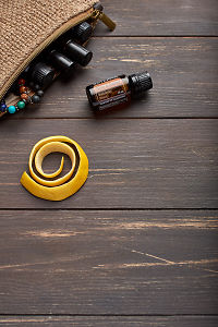 doTERRA Slim and Sassy, lemon peel and clutch with oils on brown wooden background.