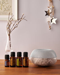 doTERRA Brevi Stone diffuser with Juniper Berry, Citrus Bliss, Lemongrass and Wild Orange essential oils and holiday decorations on a side table.