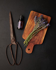 doTERRA Serenity with lavender flowers on a wooden board with vintage scissors on a black concrete background.