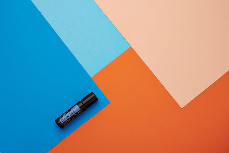 doTERRA DigestZen Touch on a blue and orange geometric background.