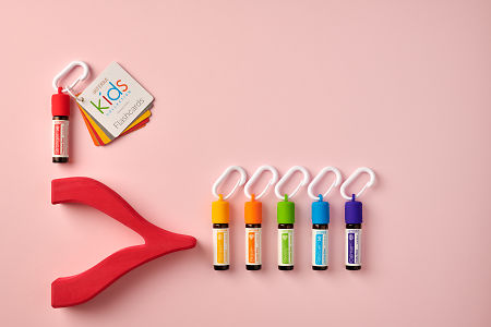 doTERRA Kids Oil Collection  oils with caps and carabiners and flashcards, featuring Stronger, on a pale red paper background.