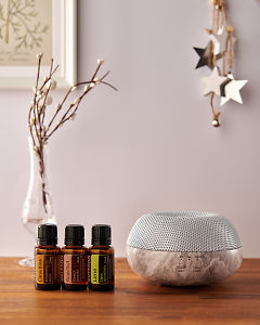 doTERRA Brevi Stone diffuser with Citrus Bliss, Grapefruit and Lime essential oils and holiday decorations on a side table.