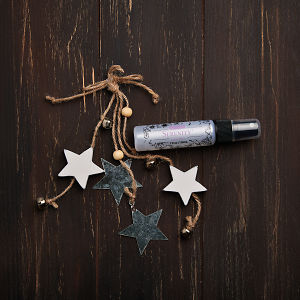 doTERRA Serenity Linen Mist with holiday decorations on a brown wooden background.