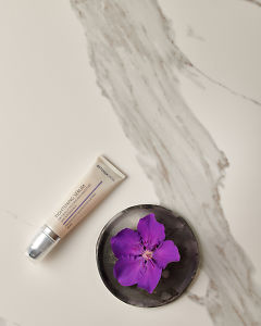 doTERRA Hydrating Cream with a purple flower in a gray ceramic plate on a white marble background.