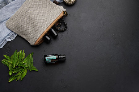 doTERRA Spearmint with clutch, accessories and mint leaves on a black concrete background.