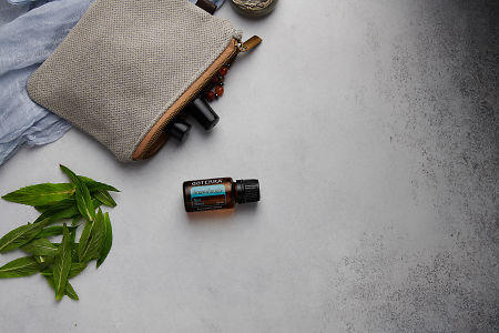doTERRA AromaTouch with clutch, accessories and mint leaves on a white concrete background.